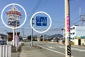 青い標識とパチンコ屋さんの看板が通りにあります